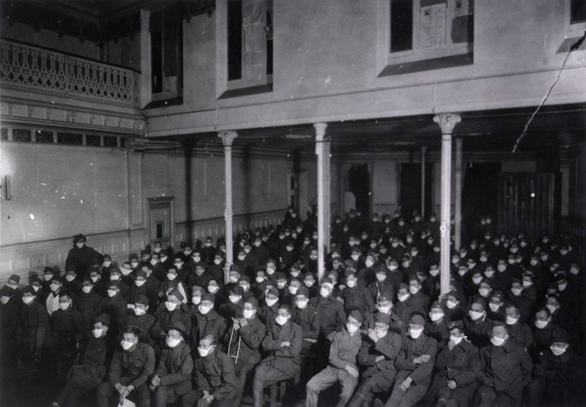 In a large hall patients sit at moving picture show wearing masks because of an influenza epidemic.