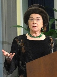 A photograph of Dr. Fee speaking at a podium at NLM.