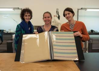 Three women pose with the completed album open in front of them.