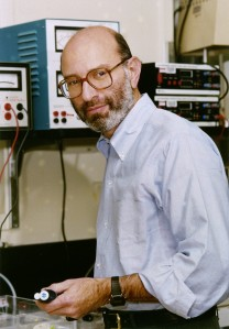 A man in a collared shirt stands in a laboratory.