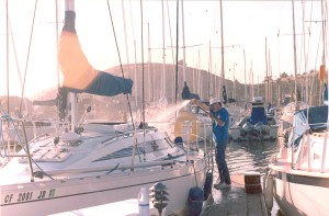 A man in jeans and a t shirt washes a sailboat at dock.