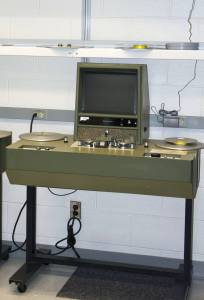 A photograph of a screening machine with a monitor and reels.