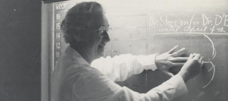 A white woman at a chalkboard