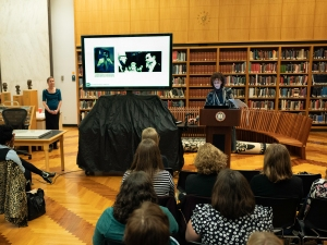 A woman at a podium by a large video screen speaks to a gathering in a book lined room.