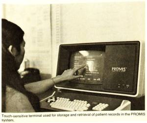 A woman touches the screen of a PROMIS data entry terminal.