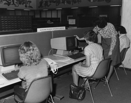Photograph of four people using computers.