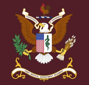 A rooster over an eagle holding a brand and arrows and a shield with an american flag and medical symbol, motto: Experientia Et Progressus.