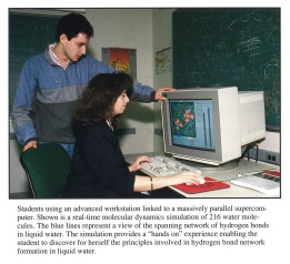 Woman sitting a computer and a man standing to her left.