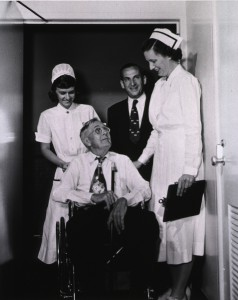 Photograph of man sitting in a wheelchair surrounded by a gentleman and two nurses.