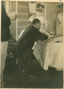 The second of a set of photos showing William Osler treating a patient, probably in Johns Hopkins Hospital. Osler is seated next to the patient's bed. The names of the other individuals are unknown.