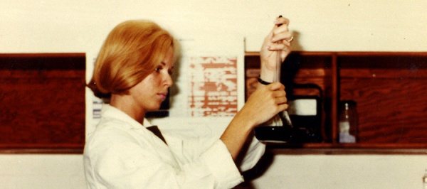 Photograph of Bernadine Healy standing in a white lab coat holding lab equipment.